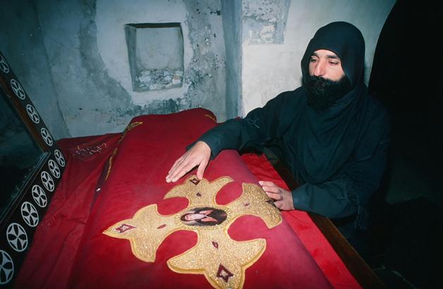 Monk venerates relics of monastery founder St. Macarius.
