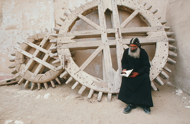 Bible reading father in courtyard with ancient drawbridge gear.