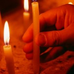 Prayer candles in a Coptic father's hand.