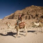 Camel rider and mounts with Royal Tombs distant
